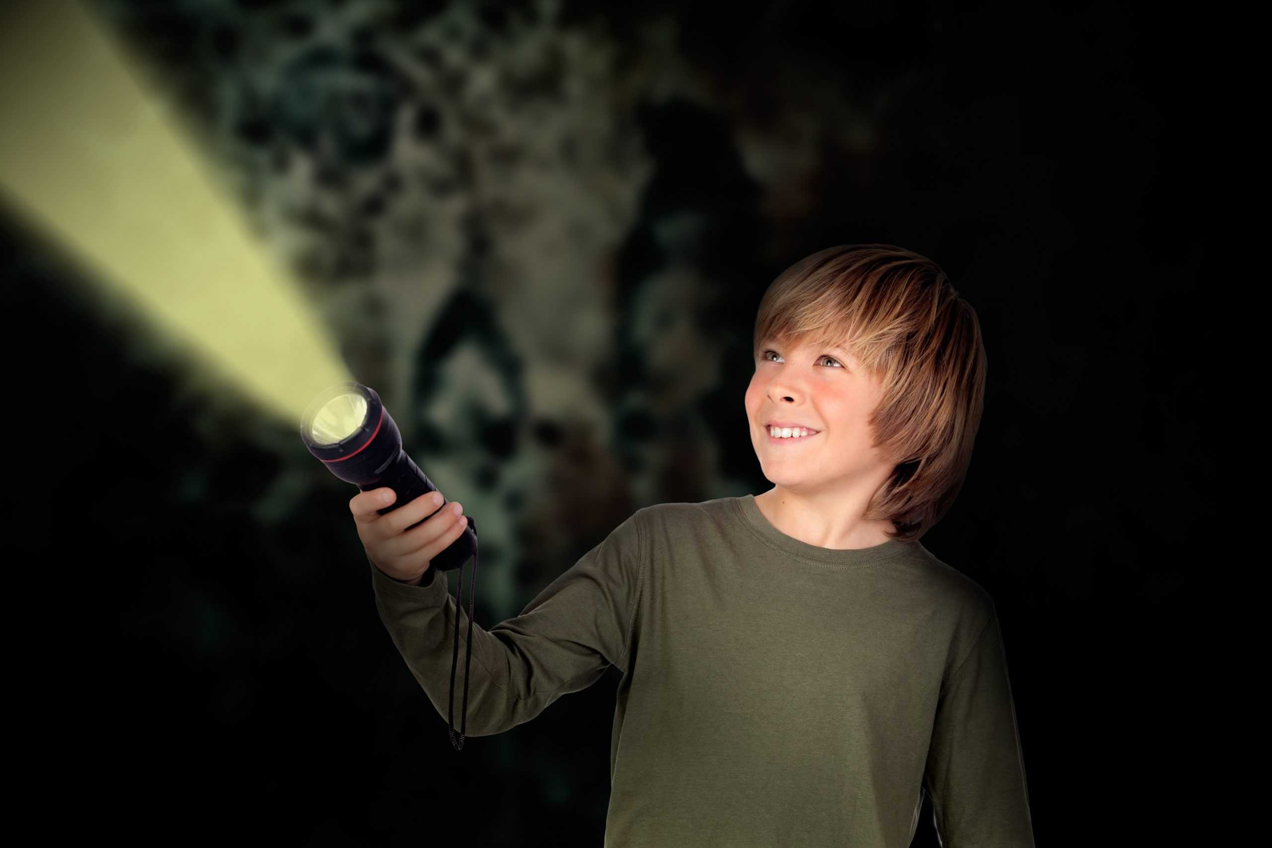Child with a flashlight looking for something on darkness background