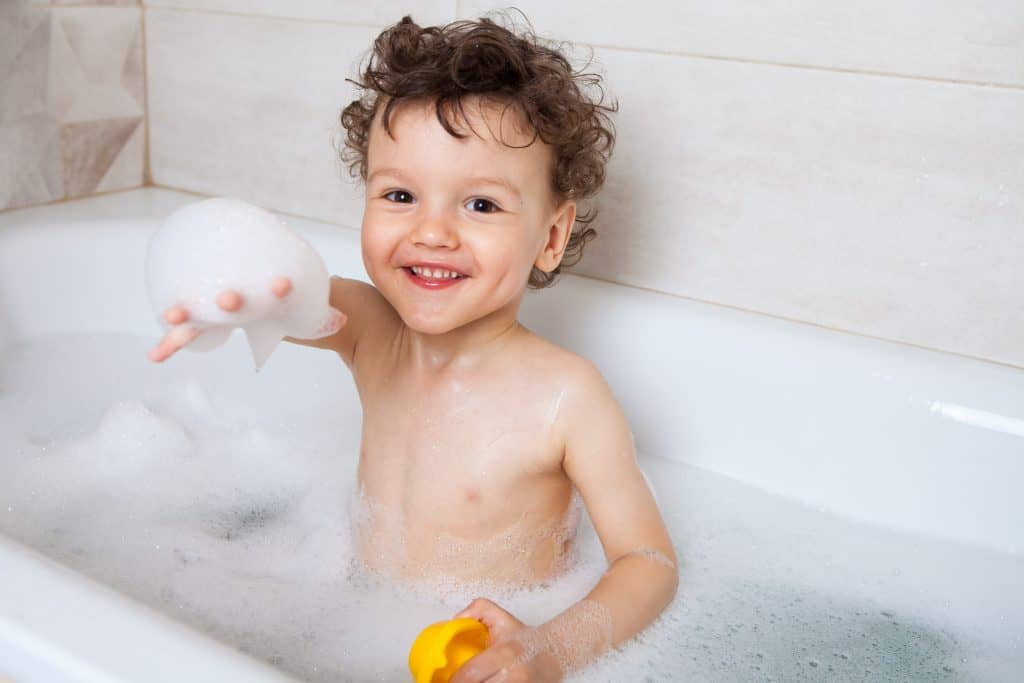 Funny happy baby, the boy bathes in the bathtub with water and foam. Pulls his hand forward with foam. Hygiene procedures as prevention of diseases and viruses.