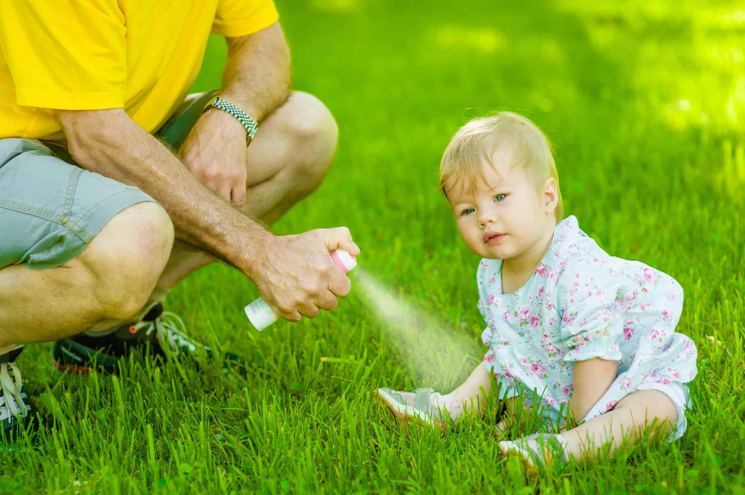 Father spraying insect repellents on skin his daughter